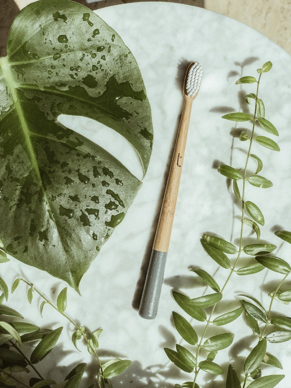 sustainable storm grey bamboo toothbrush on white marble surrounded by green plants