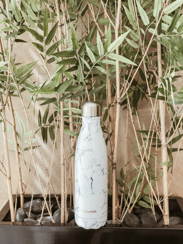 Sustainable insulated stainless steel bottle with marble design by Qwetch in front of a bamboo plant