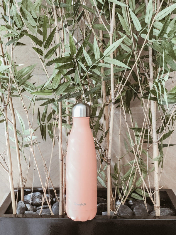 Sustainable insulated stainless steel bottle in pastel peach colour by Qwetch in front of bamboo plant