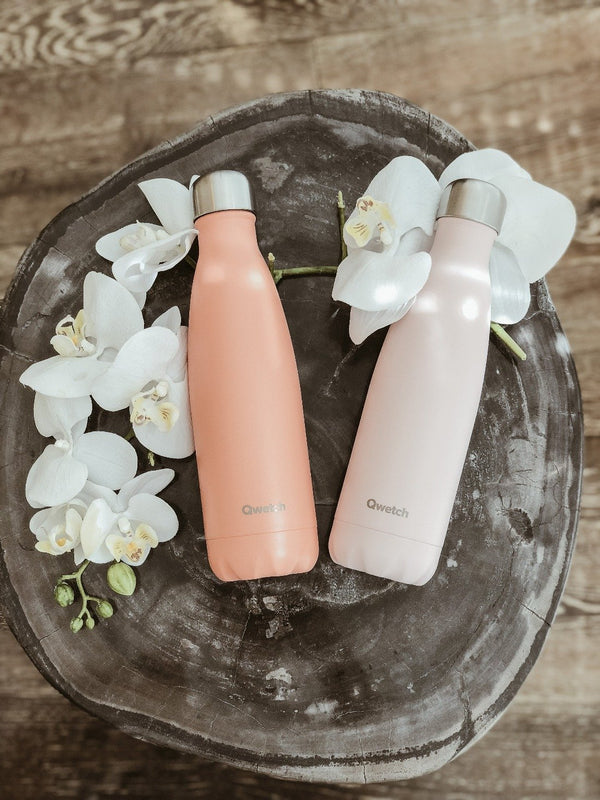 two sustainable insulated stainless steel bottles by Qwetch on a piece of wood with white orchids