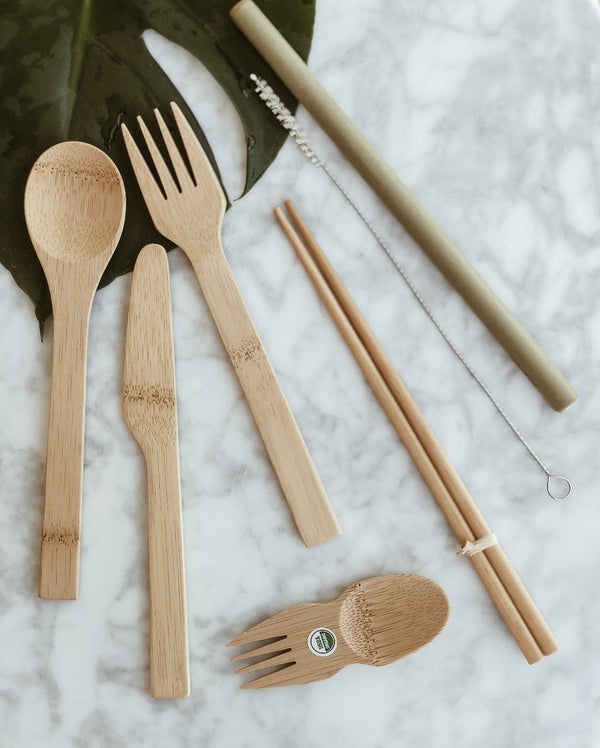 Set of sustainable eat and drink cutlery made from organic and natural bamboo containing one fork, one knife, one spoon, one spork, chopsticks and straw