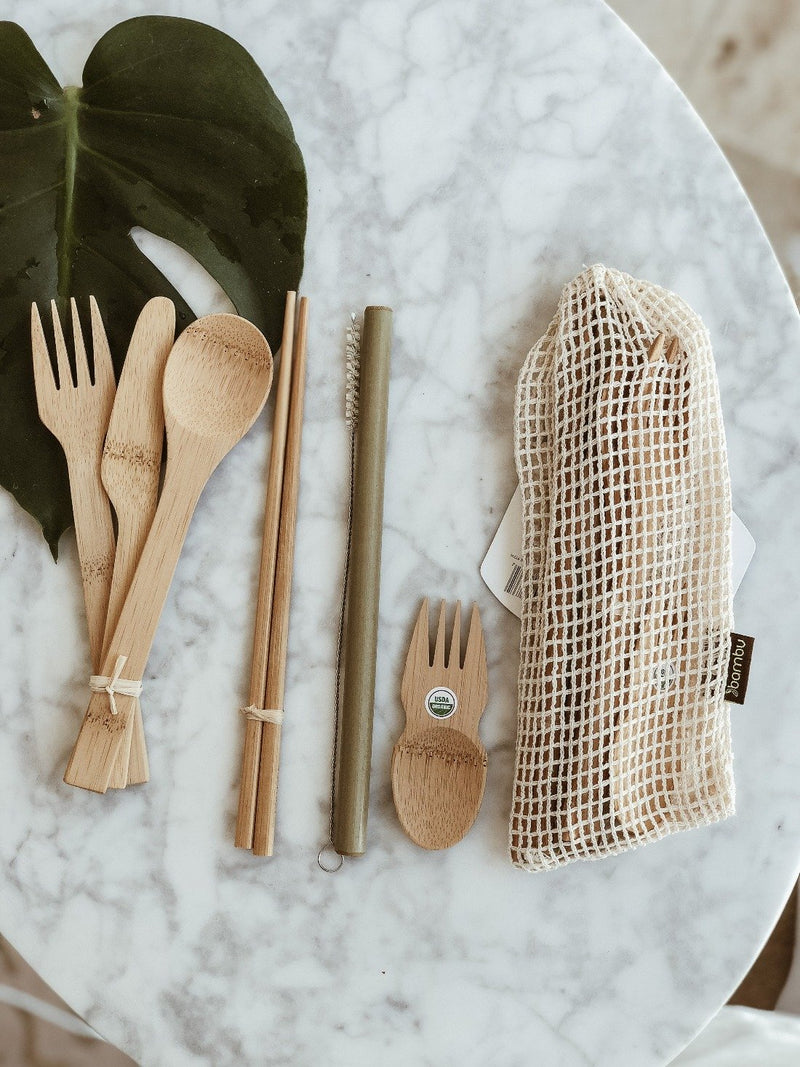 Set of sustainable eat and drink cutlery made from organic and natural bamboo containing one fork, one knife, one spoon, one spork, chopsticks and straw with its plastic-free packaging