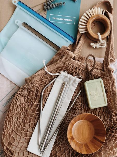 Selection of zero waste products by The Clean Market containing natural bamboo brush and bowl, reusable silicone food bags, stainless steel straw set, organic cotton net bag and vegan olive oil soap