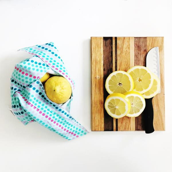 a sustainable and 100% cotton blue bento bag by Marley's Monstersholding a lemon along with a sliced lemon on a piece of wood