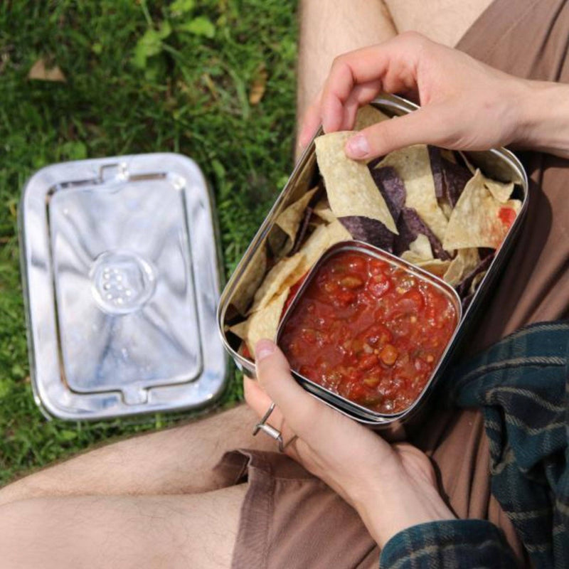 Person enjoying a meal in the park eating from a sustainable stainless steel lunchbox by The Elephant Box