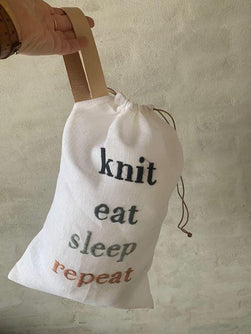 "Project bag with embroidered text ""knit, eat, sleep, repeat"", hanging"