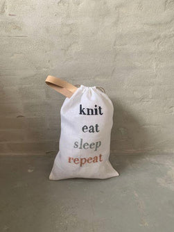 "Project bag with embroidered text ""knit, eat, sleep, repeat"", standing"