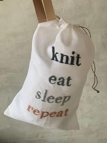 "Project bag with embroidered text ""knit, eat, sleep, repeat"""