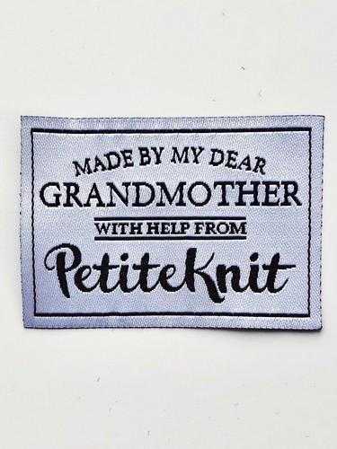 "Textile label from PetiteKnit with the text ""Made by my dear Grandmother - with help from PetiteKnit"""