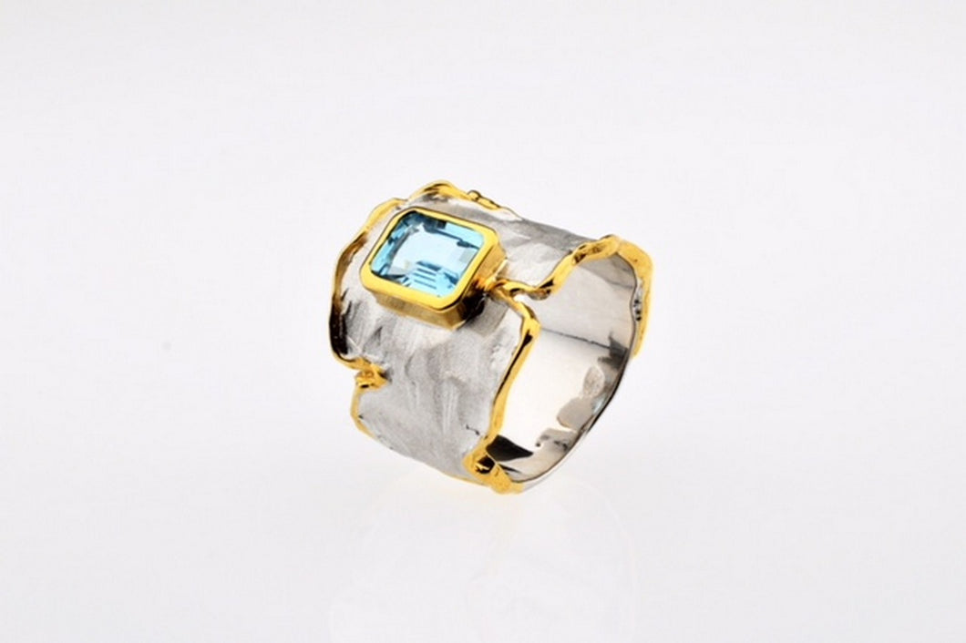 Blue topaz set in hand made, sterling silver oxidized ring, gold plated details