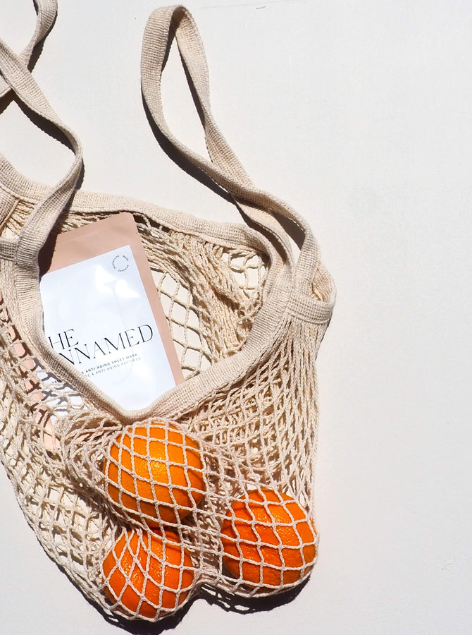 The Unnamed Skincare Brightening Face Sheet Mask in Shopping Bag with Three Oranges