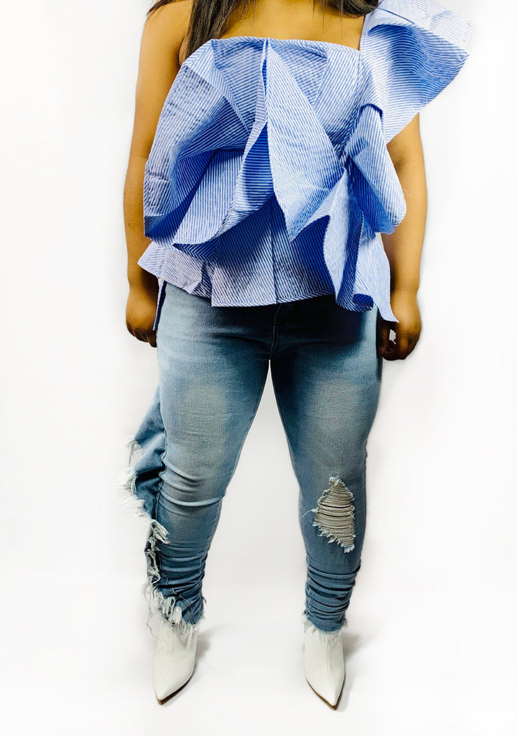 Gold x Teal ruffle skinny leg jeans. Chic skinny leg jeans with distressed ruffles cascading down one pant leg.