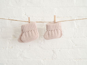 Nivas Collection, Cashmere baby booties, baby booties hung on string, White brick wall, cashmere baby socks