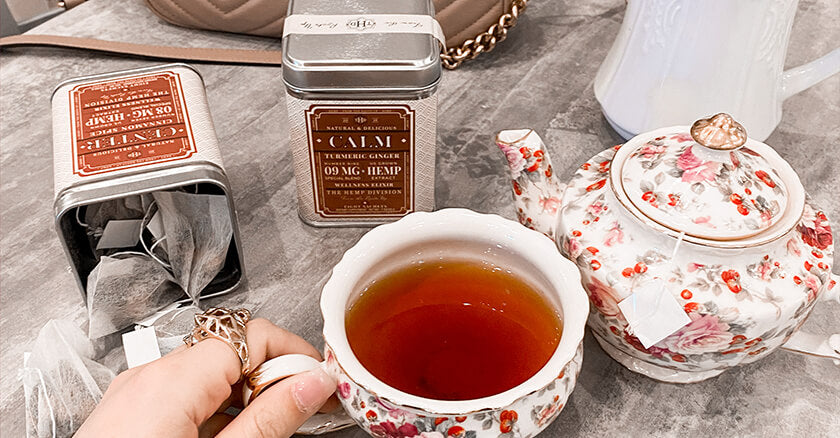 cup of tea with teapot and tins