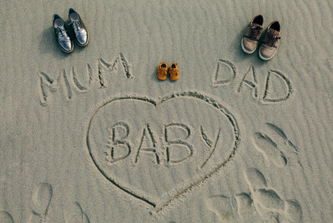 pregnancy announcement written in beach sand