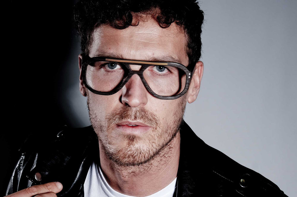 Male model wearing the JOIUSS Jim navigator styled glasses frame in the dark wood effect finish.