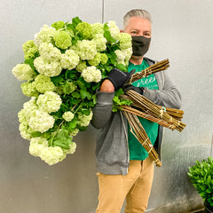 Carlos Franco with flowers and face mask