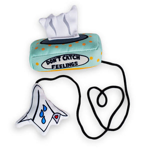 "A tissue box cat toy with ""Don't catch feelings"" written on the box and a cord connecting it to a tissue with three blue drops and a small heart. An original from the Lucky Bubs pet store."