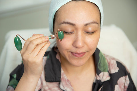 woman using facial roller puffiness eye lymphatic drainage