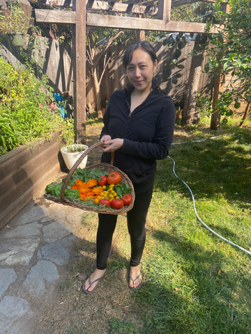 Patty of Free Flow Botanicals proudest moment of 2020 first vegetable garden holding basket of harvest