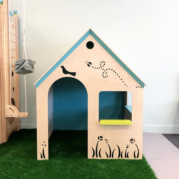 Wooden Playhouse for children in grassy indoor play area