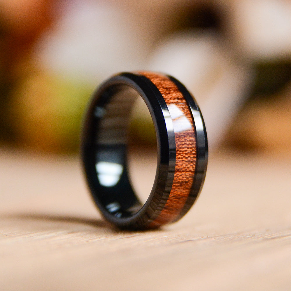 An elegant and modern black tungsten ring with koa wood inlay from Urban Designer.