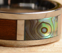 Close view of abalone shell koa and tungsten wood wedding band from Urban Designer.