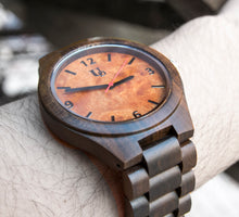 A natural wood watch made of sandalwood with an orange face and a red second hand from Urban Designer.
