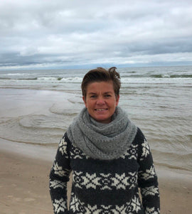 "Katrine Hannibal by the sea wearing her ""Cloud"" super light knitted shawl with lace pattern, made in grey Silk Mohair"
