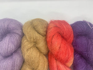 4 skeins of various colors of naturally dyed mohair yarn. 2 purple, one brown, and one a fiery orange.
