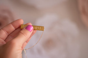 Image of hand holding braille necklace in gold plated that says it is well