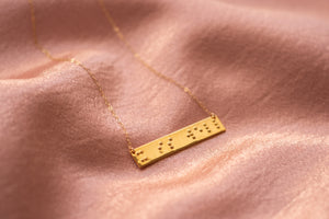 Image of braille necklace in gold plated that says it is well