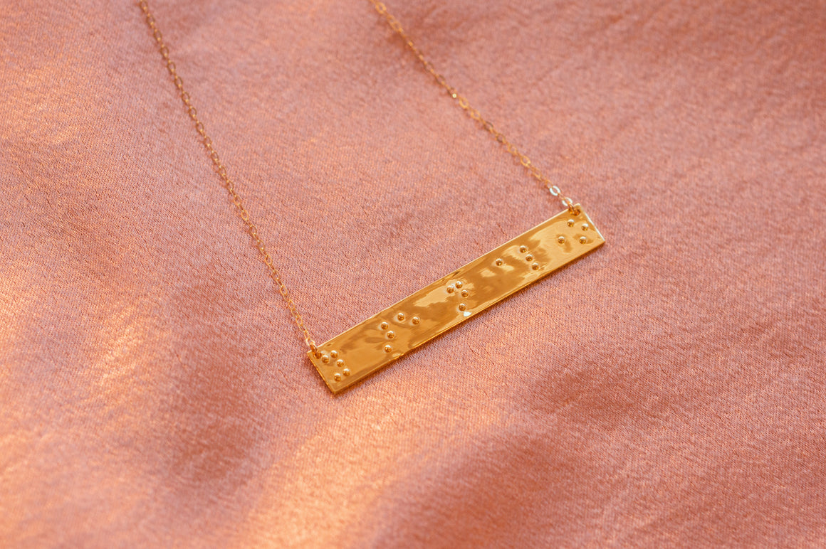 Picture of silver and gold braille necklaces that say you are not alone