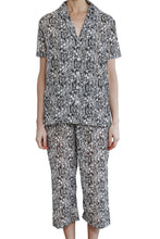 Load image into Gallery viewer, Imogen cotton silk pyjama set with black and white floral design, has 3/4 length elasticised drawstring pants with a short sleeve pyjama top with buttons down the front. front