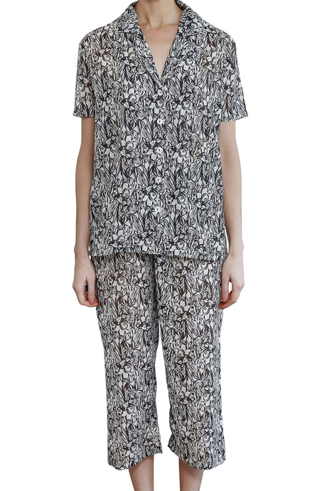 Imogen cotton silk pyjama set with black and white floral design, has 3/4 length elasticised drawstring pants with a short sleeve pyjama top with buttons down the front. front