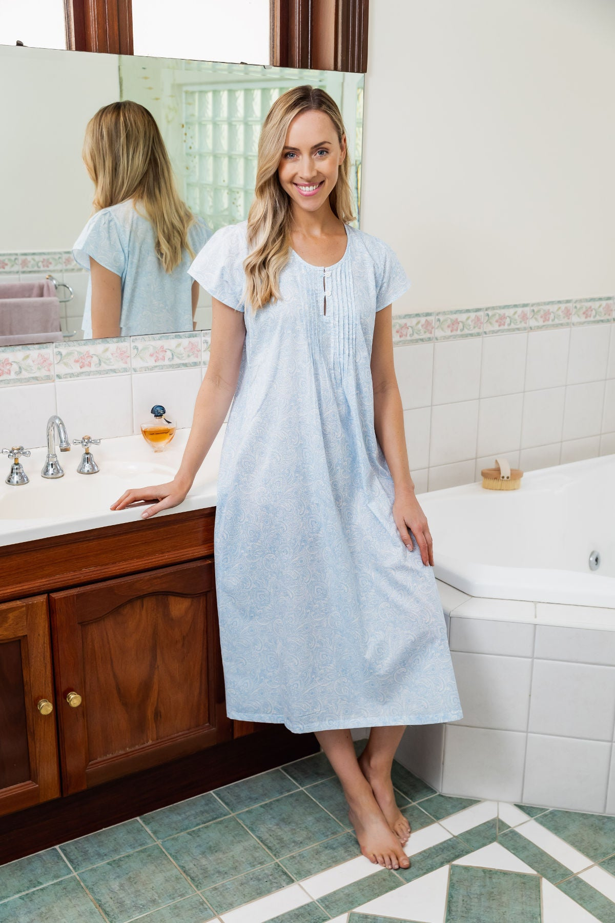 The Joyce cap sleeve nightie has a pleated bodice trim and two front opening buttons, with a soft paisley blue pattern on a white background, falling to a 3/4 length relaxed fit ensuring you drift off to a sleep in comfort.