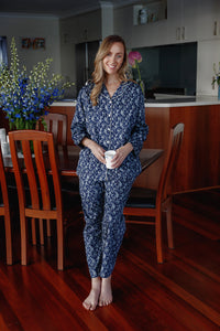 "Our ""Rosalie"" cotton pyjama set features a white floral pattern with a navy background, white piping, long sleeves, and an elasticised waist and drawstring."