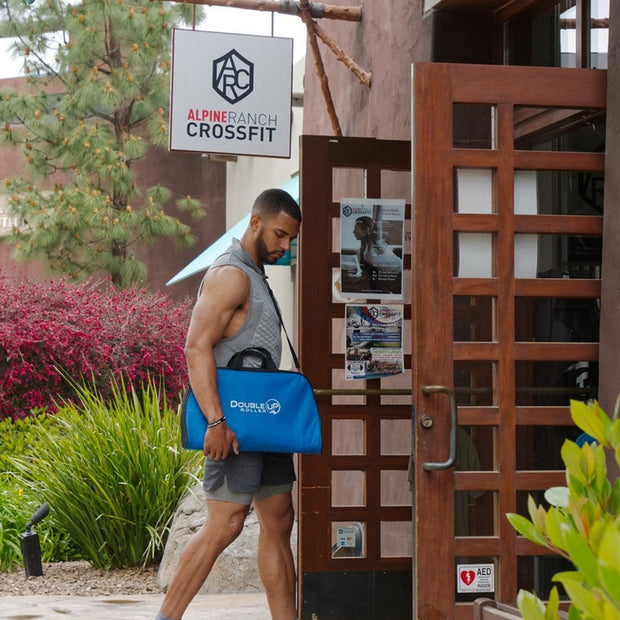 Athlete entering a CrossFit gym for a workout with DoubleUP carrying bag over his shoulder