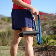 Runner rolling her legs for warm-up and stretching from a standing position with DoubleUP frame loaded with TuneUP smooth medium-density foam rollers