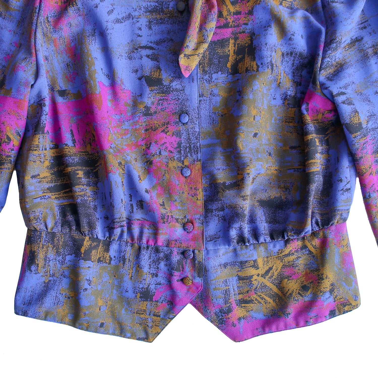 Second Room Shop Vintage. Shop vintage, shop sustainable. Vintage blouse with tie at the neck, can be worn on its own as a top, or as a light jacket. The tie is fully attached to one side, so it could still be tied with the blouse unbuttoned. Has a great abstract pattern in purple, blue, black and gold, and fully buttons down the front. Has two buttons on each cuff, a standing collar with pleated detail, and no shoulder pads. Slight gathered detail on the shoulder seam. A truly unique and beautiful piece!