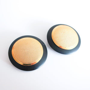 "Second Room Vintage Clothing. Vintage oversize matte black metal stud earrings, with gold tone center with textured grid pattern. Earrings are just under 2"" across. Original earring backs have been replaced with new, clear silicone backings. Free North American shipping on all orders."