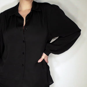 Second Room Shop Vintage. Shop vintage, shop sustainable. Vintage long sleeve black blouse, with gathered detail at shoulder and chest, and one button closure at each cuff. Made in Canada.