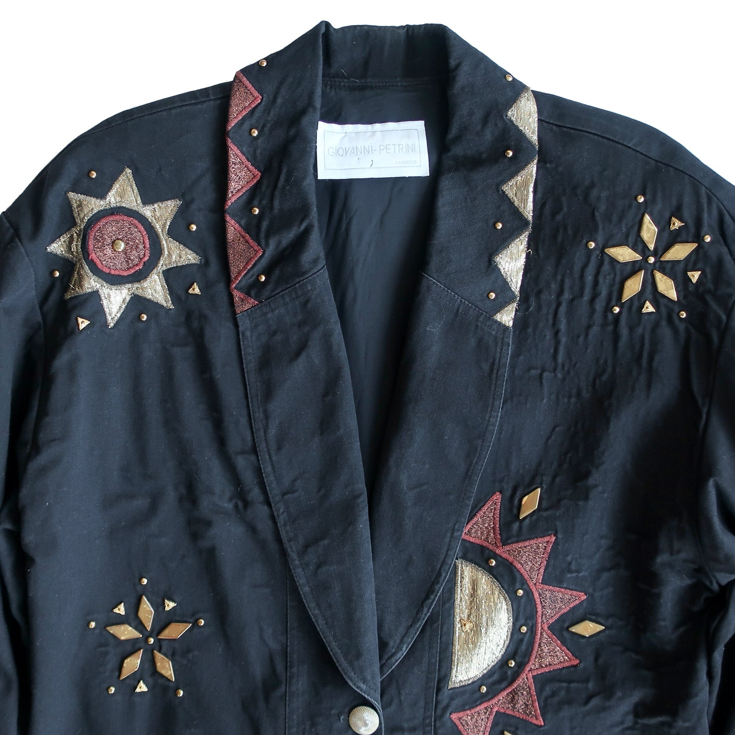 Second Room Vintage Clothing. Vintage black cotton blazer with amazing copper and gold metallic thread designs, and round and triangle metal studs. Fully lined with sewn in shoulder pads, two front pockets, and two button closure. Free North American shipping on all orders.