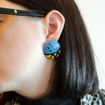 "Second Room Vintage Clothing. Vintage blue and yellow round studs with abstract painted 80s design. Earrings are 1.25"" across. Original earring backs have been replaced with new, clear silicone backings. Free North American shipping on all orders."