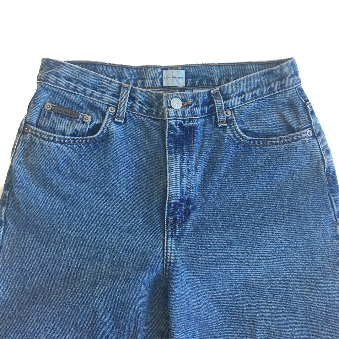 "Second Room Shop Vintage. Shop vintage, shop sustainable. Classic vintage 1990s Calvin Klein jeans. Five pocket style, zipper fly, belt loops, and leather CK patch on back waistband. Style on label is ""classic 5 pocket jean, double stonewash"". 12"" rise, with 7"" zipper, made in USA."
