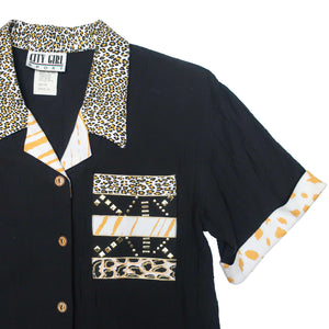 Second Room Vintage Clothing. Vintage black short sleeve button up blouse, with mixed animal prints on the collar, cuffs, and front pocket. The pocket also has gold metal stud details. Free Shipping on all orders within North America.