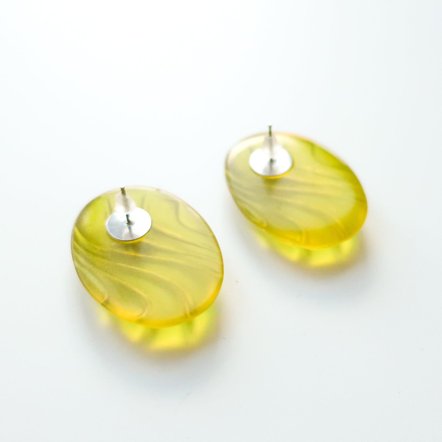 "Vintage clear green acrylic stud earrings with wavy pattern. Earrings are 1"" wide and 1.25"" tall. Original earring backs have been replaced with new, clear silicone backings."