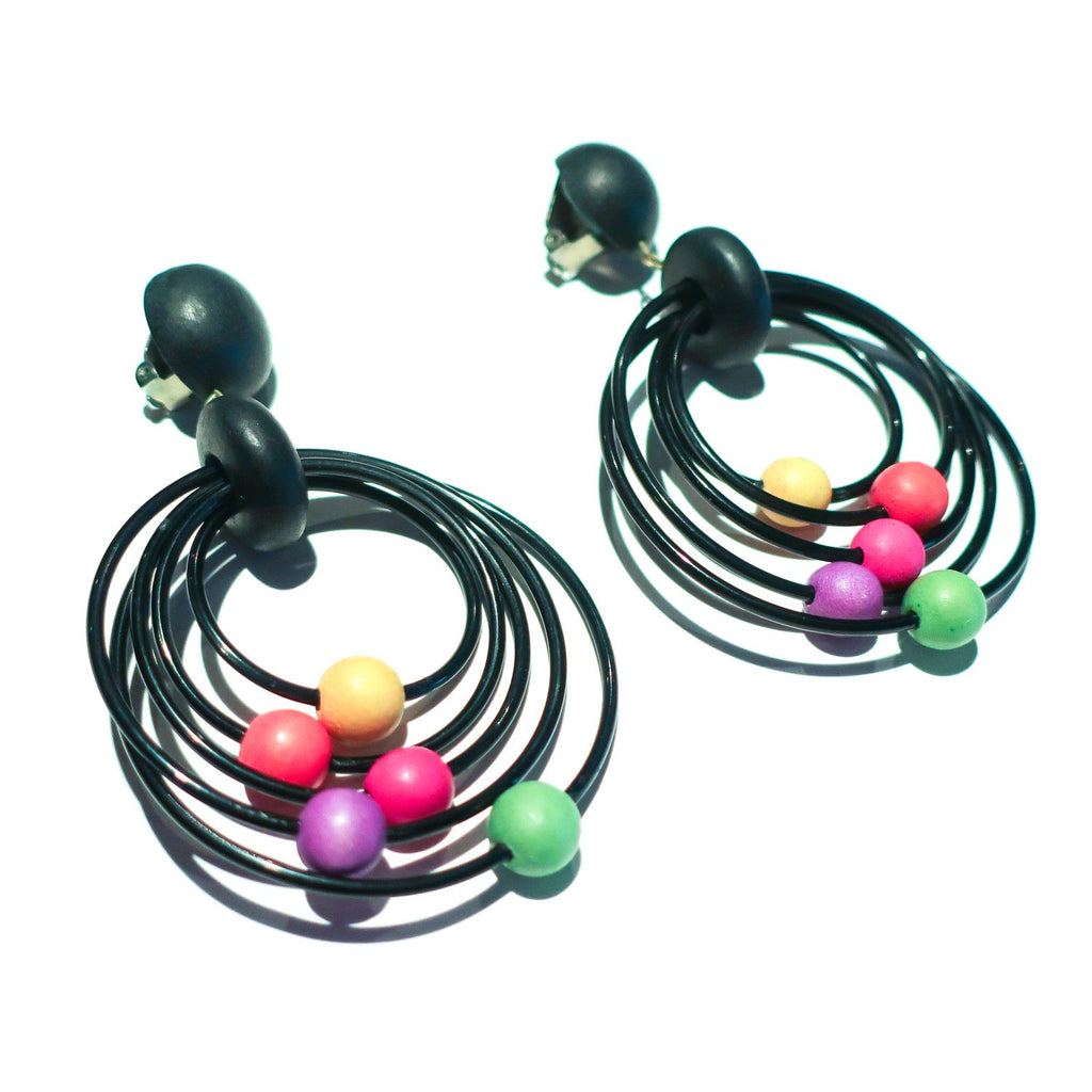"Second Room Vintage Clothing. Make a statement with these black, multi hoop clip on earrings, with painted wood bead details in yellow, orange, pink, purple and green; 2.5"" across and 3.5"" long. Free North American shipping on all orders."