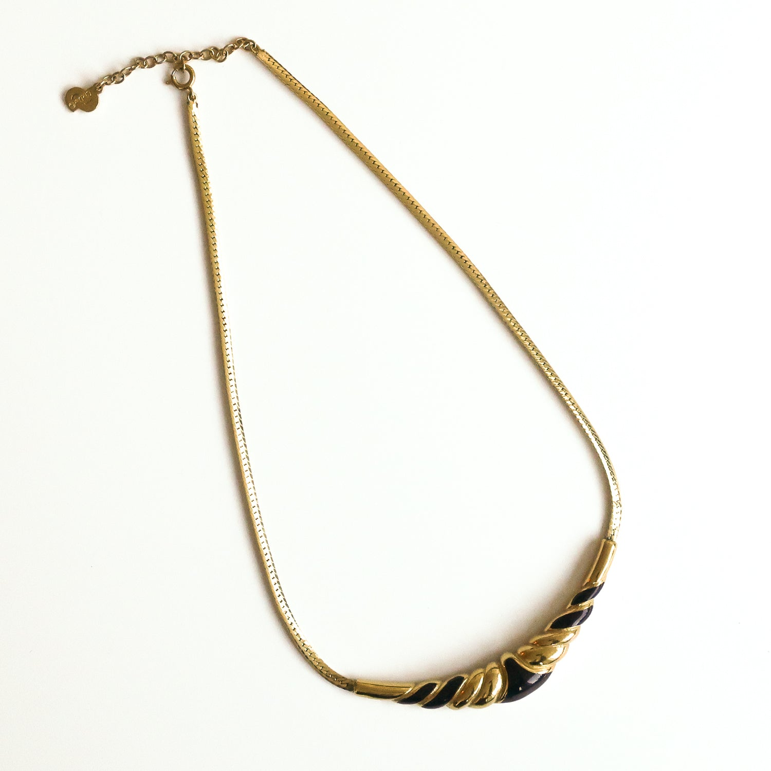 "Second Room Shop Vintage. Shop vintage, shop sustainable. Vintage gold tone and black enamel Christian Dior necklace from the 1980s. This necklace is a short choker style; hanging length is 6.5"", total length is 16"" to 18"", as there is a 2"" extension chain at the back of the clasp. The gold and enamel pendant is 3"" wide, and the chain is a linked herringbone style."