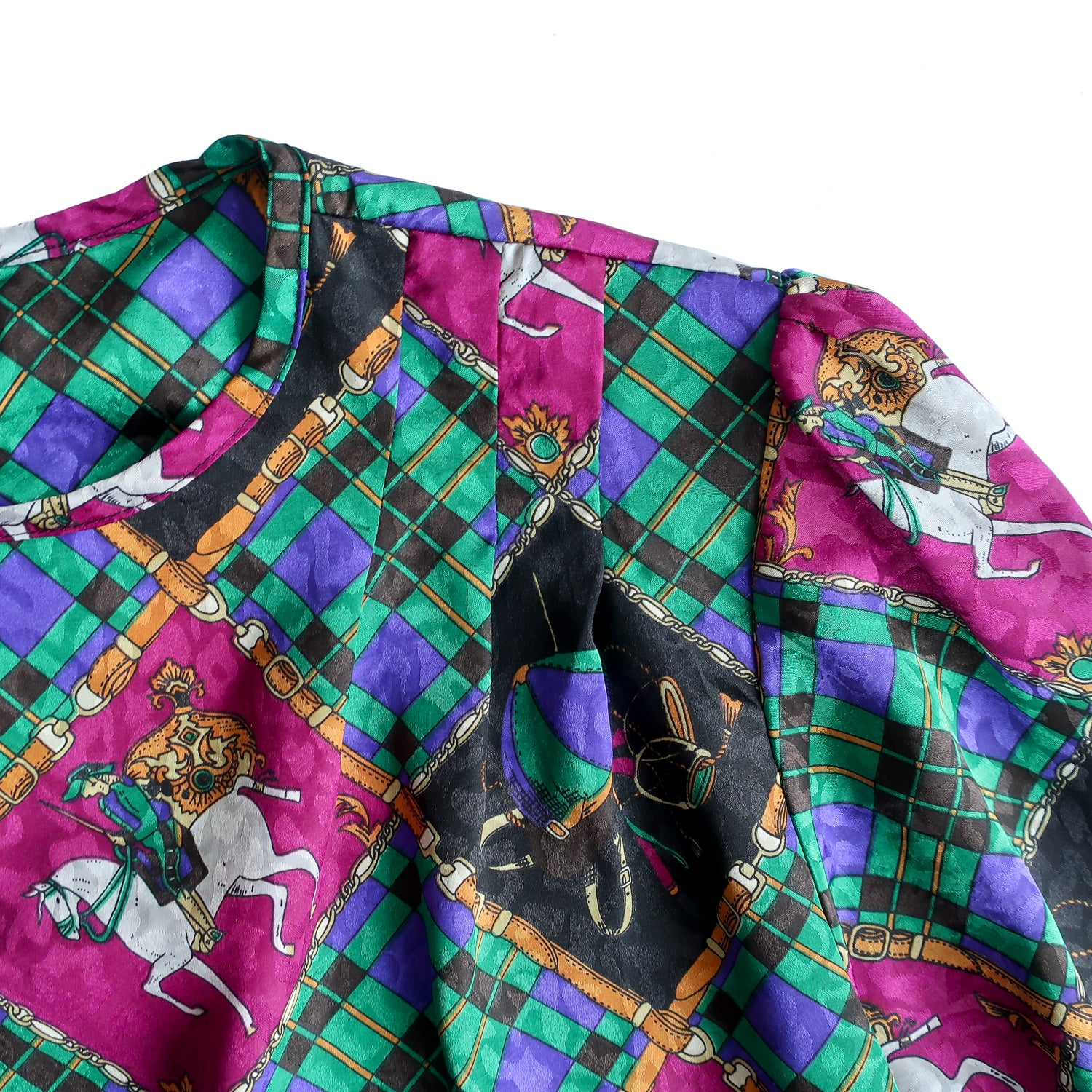 Second Room Shop Vintage. Shop vintage, shop sustainable. Vintage long sleeve blouse with the most amazing Gucci inspired equestrian print, in jewel tones of green, purple, blue, and gold. This blouse has a crew neck, with two buttons at the back of the neck for closure, and a lovely pleated detail at the front shoulders. It has one button at each cuff, and has shoulder pads, which could be easily removed.